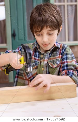 Concentrated boy in checkered shirt hammering nail in wooden plank