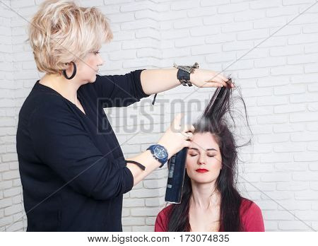 beauty, hairstyle and people concept. Young woman with middle aged hairdresser with hair spray fixating hairdo at salon. Stylist makes hairstyle using spray lacquer fixing. Hairdresser with hair spray