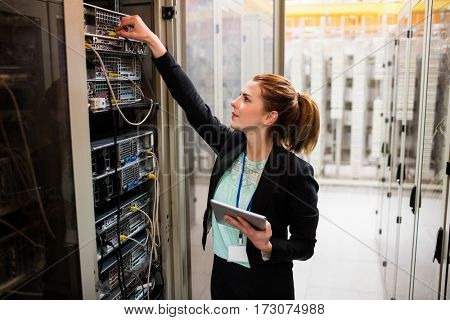 Technician holding digital tablet while examining server in server room