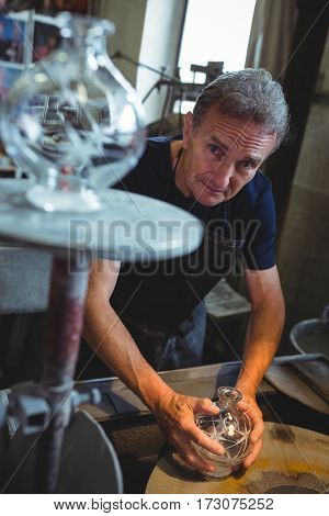 Portrait of glassblower working on a glass at glassblowing factory