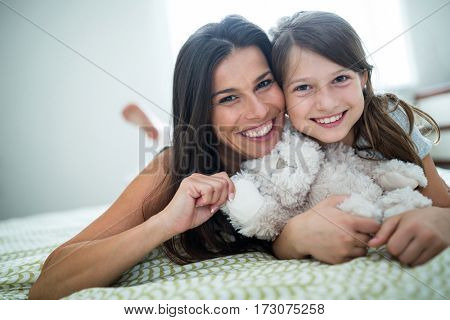 Portrait of mother and daughter lying in bedroom at home