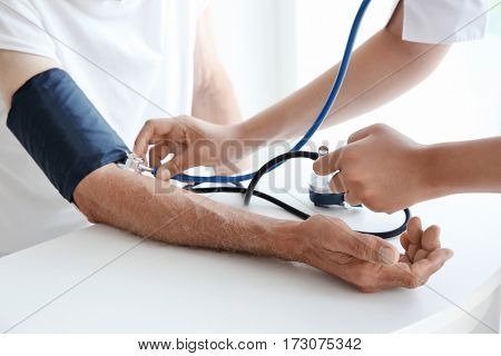 Nurse helping senior with measuring pressure on wooden table
