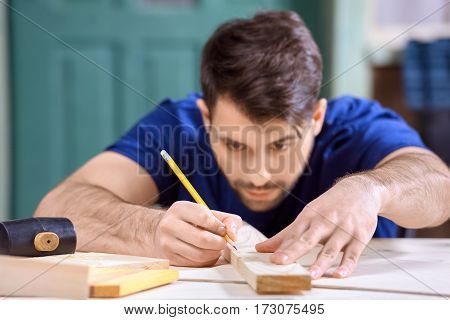 portrait of concentrated carpenter working taking measures of wooden plank