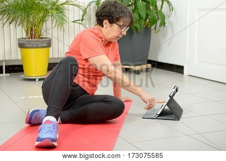 Middle-aged woman doing fitness exercises with tablet at home