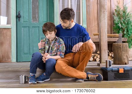 man cheering up upset boy while sitting on porch