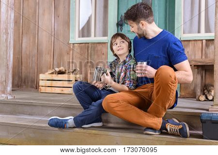 man and boy with cups of tea looking at each other while sitting on porch