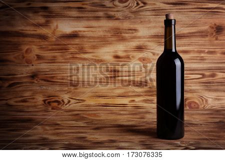 Wine bottle with cork on wooden background