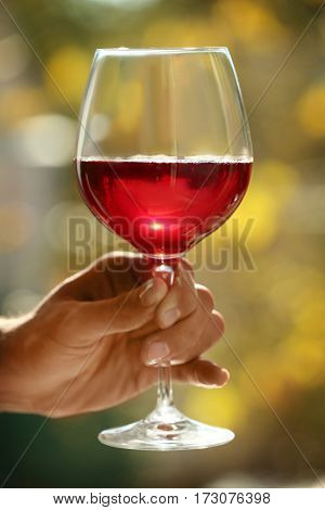 Male hand holding glass with wine on blurred natural background