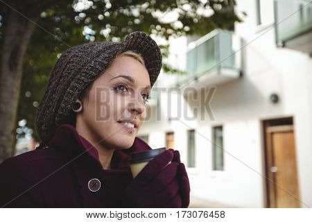 Woman smiling and holding a cup of coffee in street