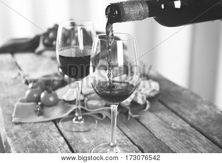 Pouring wine into glass on wooden table, toned in black and white