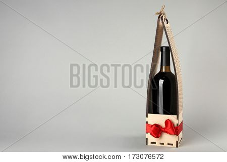 St. Valentine's Day concept. Wine bottle in gift box with satin ribbon on light background
