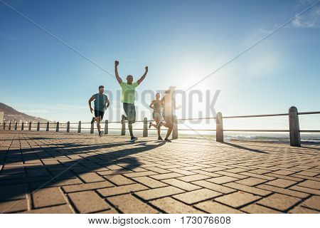 Group of young people running along seaside promenade. Runners training outdoors by the seaside.