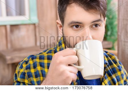 portrait of man drinking tea on porch and looking away