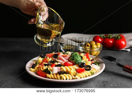 Female hand pouring oil over pasta salad on table