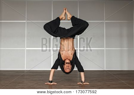 Handsome Man In Black Clothes Doing A Workout On The Hands.