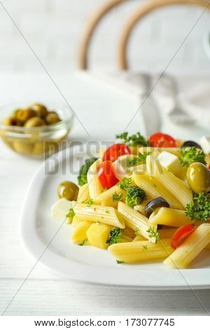 Pasta salad with tomatoes and olive on wooden table