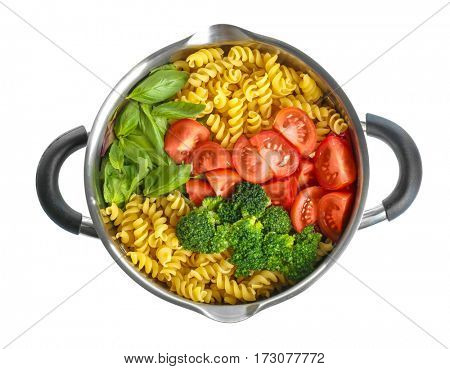 Pasta Fusilli with vegetables and basil in saucepan on white background