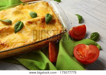 Traditional lasagna in glass baking dish, tomatoes and napkin on table