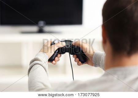 Teenager playing videogame at home, closeup