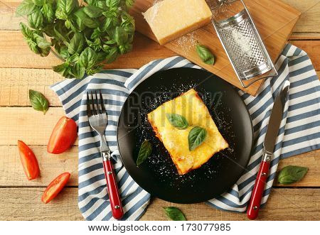 Black plate with delicious lasagna and striped napkin on wooden table