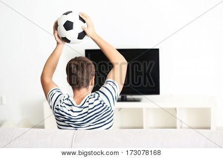 Teenager watching football match at home