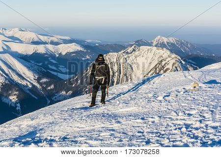 Mountaineer With Ice Axes And Backpack In The Mountains In Winter.