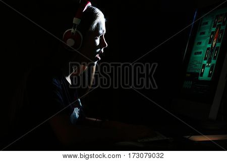 Pretty teenager playing computer game at home late in evening