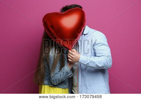 Cute young couple with balloon in shape of heart on color background
