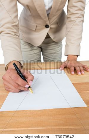 Mid section of businesswoman filling mortgage contract form against white background