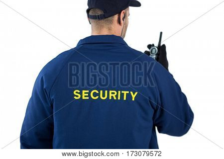 Rear view of security officer talking on walkie-talkie against white background