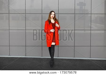 Stylish Fashionable Girl In Red Coat And Black Boots Standing Near A Gray Wall