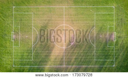 Football pitch, aerial view. Aerial drone photo looking down vertically onto an empty football (soccer) pitch with shadows cast by the low sun.