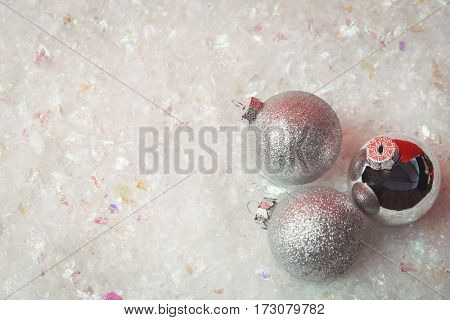 Three christmas baubles on snow during christmas time