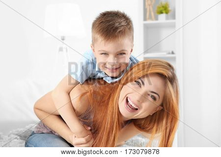 Happy mother and son playing and at home