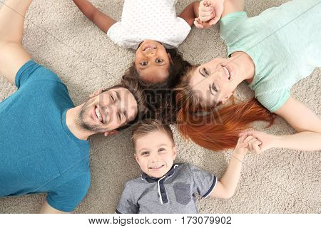 Happy interracial family lying on floor