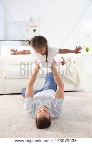 Happy father playing with African American daughter on floor