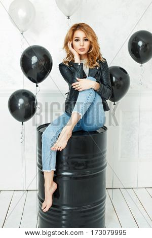 Pretty Sexy Woman In Black Leather Jacket In Blue Jeans Sitting On A Black Metal Barrel In The Studi