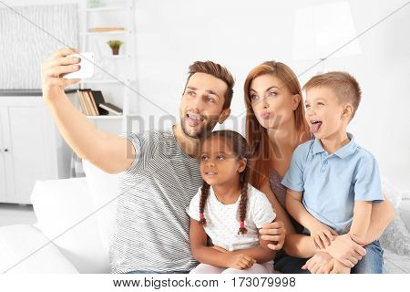 Happy interracial family making selfie at home