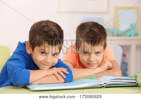 Cute little boys with book sitting at table, closeup