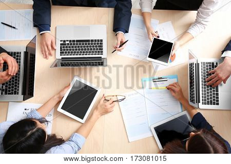 Group of business people working at desk, top view