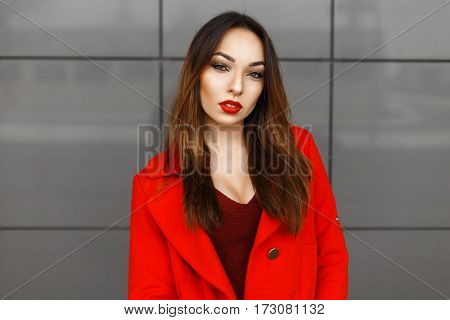 Beautiful Elegant Woman With Red Lips In Red Coat At The Wall