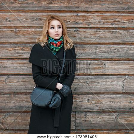 Beautiful Young Blonde Woman In A Black Coat And A Stylish Handbag Near The Wooden Walls.