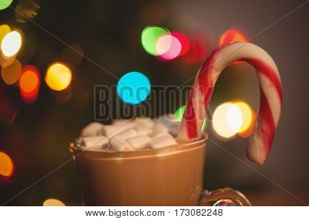 Cup of coffee with marshmallow and candy cane on wooden table
