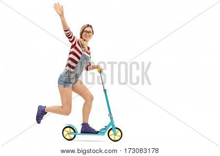 Full length portrait of a cheerful female hipster riding a scooter and waving isolated on white background