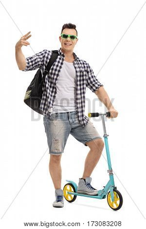Full length portrait of a cheerful cool man with a scooter gesturing with his hand isolated on white background