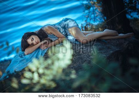 Fashion Art Photo. Model Girl Portrait in Moonlight at Night. Sexy Glamour Mystical Beautiful Woman in blue dress laying on rock over water background. Beautiful fashion creative shot of seductive multi-racial Asian Caucasian sexy female. Girl looking at