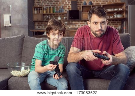 focused father and son playing video game at home