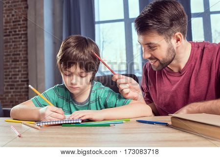 portrait of father helping concentrated son doing homework