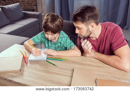 high angle view of father helping concentrated son with homework