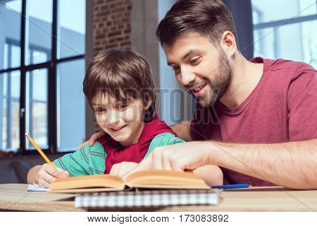 portrait of smiling father helping son with homework